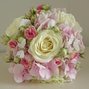 A bouquet of large ivory roses, small pink roses and pink Hydrangea